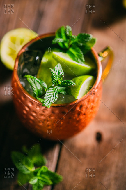 Moscow mule, cocktail with vodka, ginger beer, lime and mint over a wooden table