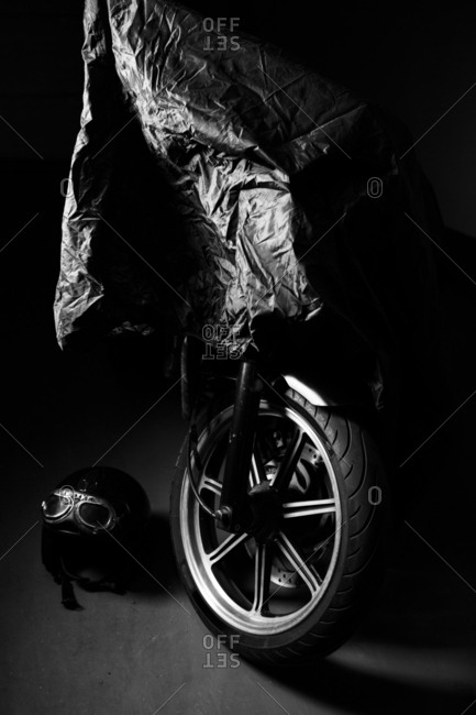 Black and white shoot of a covered retro motorbike at garage