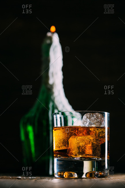 Glass of whiskey on a wooden table with a bottle full of wax froma a candle