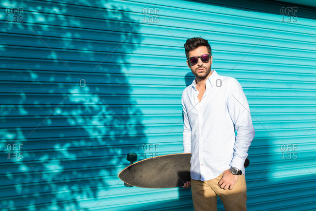 Young handsome brunet in casual and sunglasses posing with skateboard against turquois panel wall