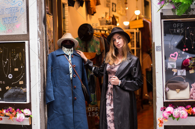 Young trendy girl posing near mannequin wearing coat in doorway of shop