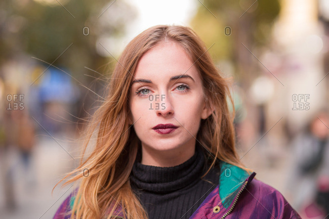 Young stylish girl with dark lipstick looking at camera on blurred street background
