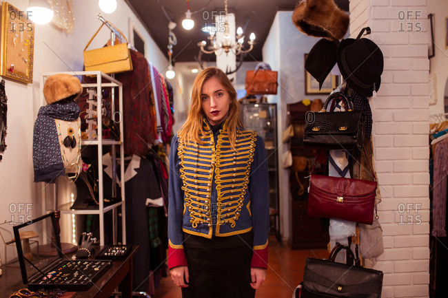 Young trendy girl wearing uniform jacket and looking at camera in accessory shop