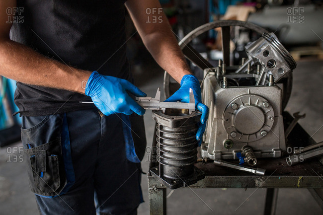 Close-up of a mechanic  using a vernier caliper to measure a cylinder from a compressor engine