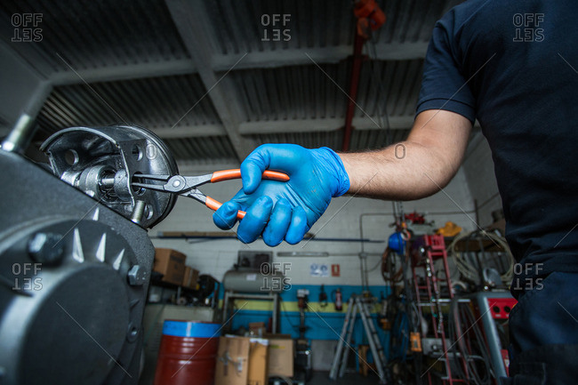 Close-up of a mechanic  using needle-nose pliers to fit a circlip inside a piston from a compressor engine