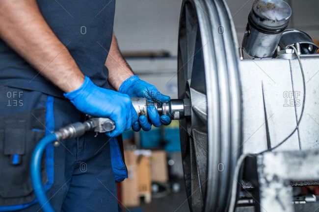 Close-up of a mechanic using an air impact wrench to detach a flywheel from a compressor engine