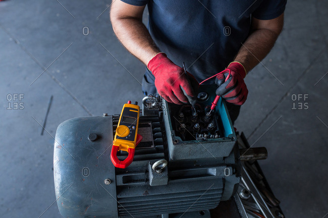 close-up of a mechanic using a multimeter to test an electric motor