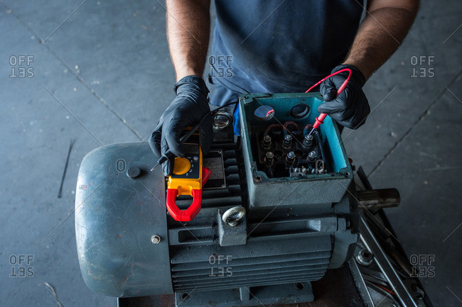 close-up of a mechanic using a multimeter to test an electric motor coil from a compressor engine