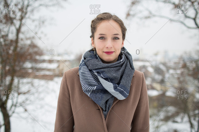 Portrait of young pretty woman in outwear looking at camera on blurred snowy landscape