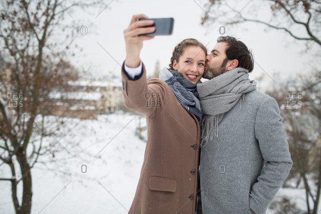 Young beautiful couple kissing and smiling and making selfie on blurred snowy landscape