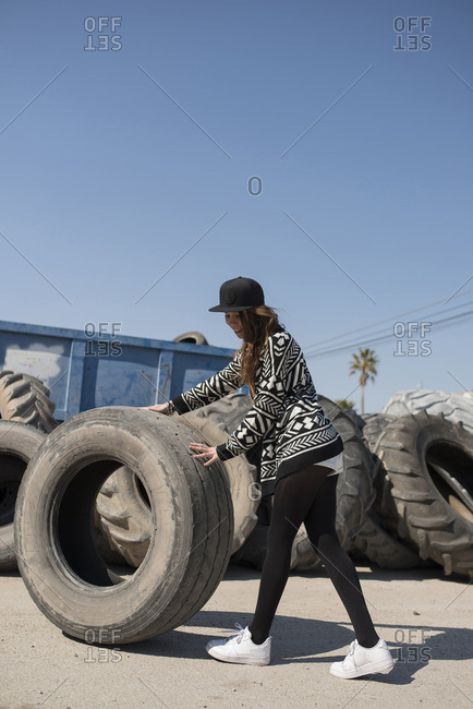 Young girl walking and pushing big truck tire on background of tires in big pile