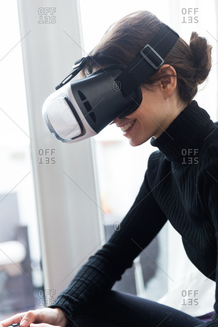 Woman holding VR headset while sitting on purple sofa