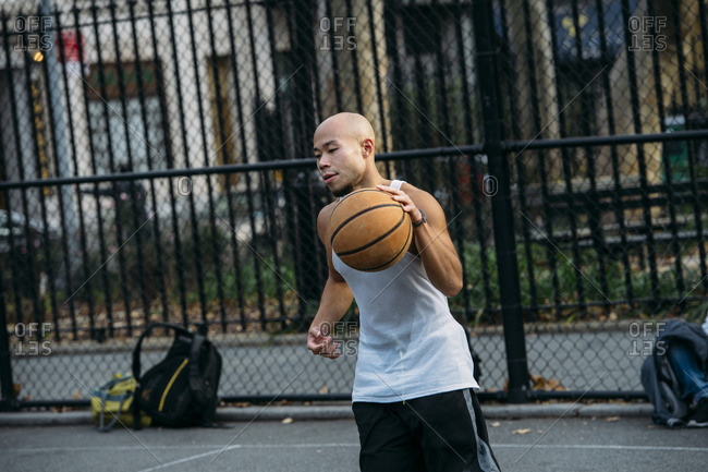 Asian man playing basketball in street court