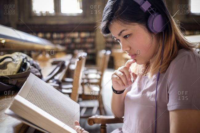 Chinese woman in library reading book and listening to headphones