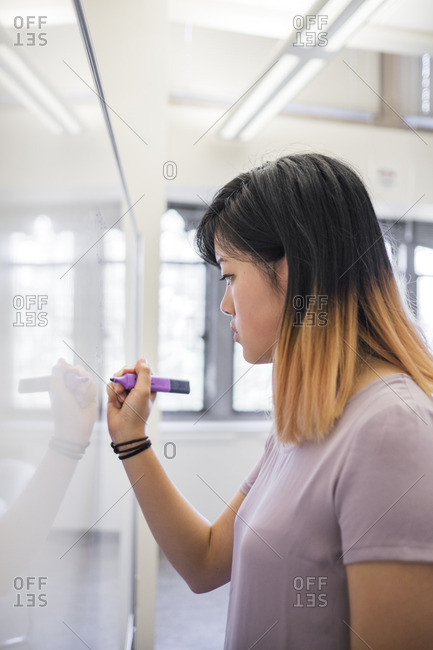 Chinese woman writing on whiteboard with marker