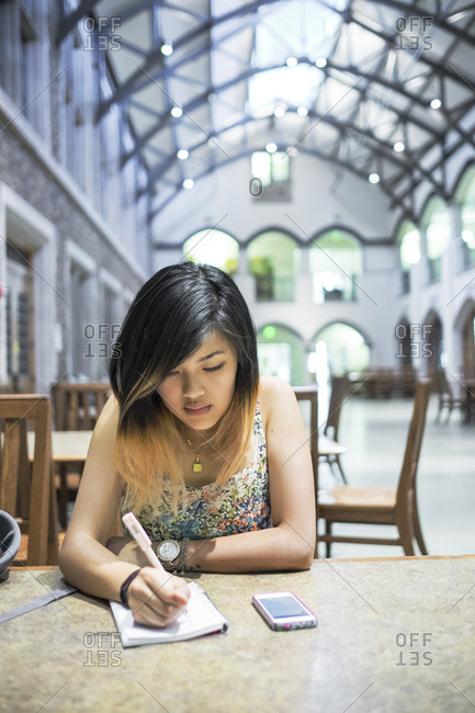 Chinese woman sitting in library writing in notebook