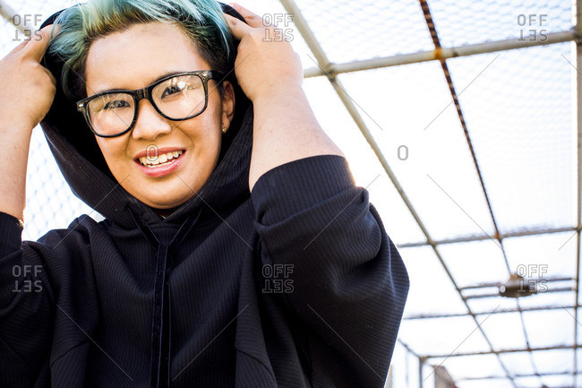 Portrait of smiling androgynous Asian woman wearing hoodie