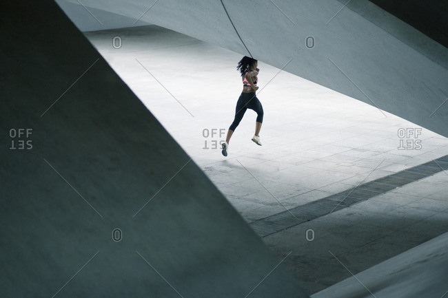 Mixed Race woman running under urban structure