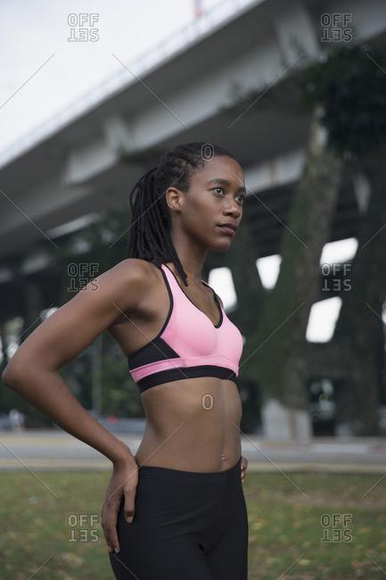 Serious Mixed Race woman wearing pink sports-bra near bridge