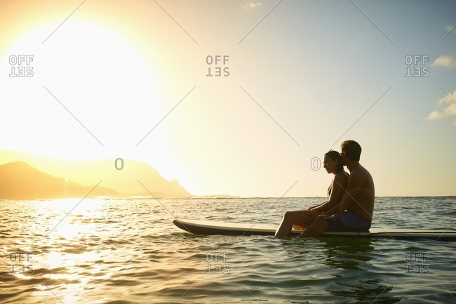 Couple sitting on paddleboard in ocean at sunset