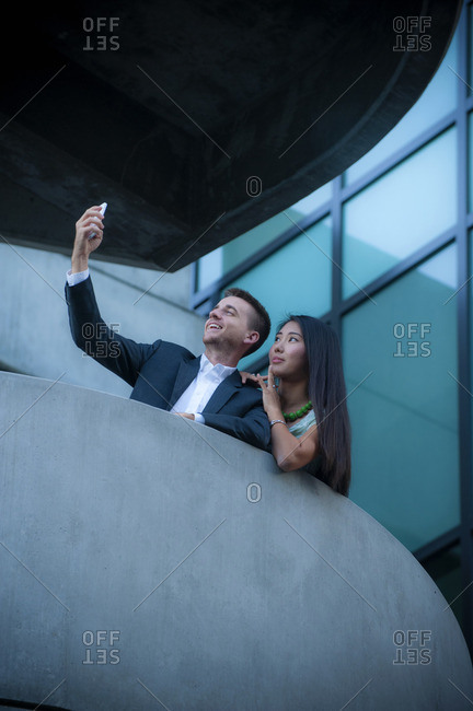 Low angle view of couple on balcony posing for cell phone selfie