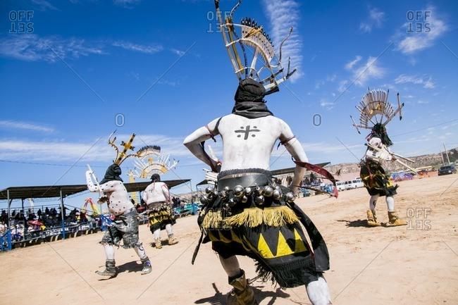 Apache men dancing in traditional regalia