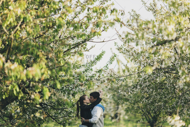 Caucasian couple kissing near trees