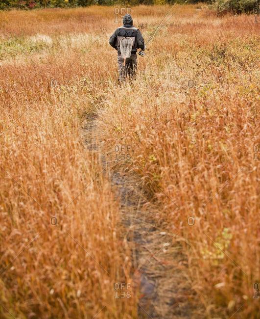 Caucasian man walking on path carrying fishing rod