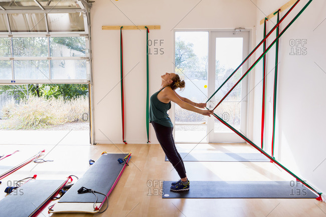 Caucasian woman using resistance bands in gymnasium