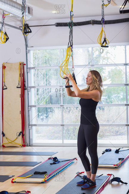 Caucasian woman adjusting resistance bands in gymnasium