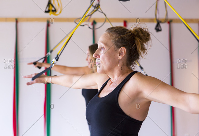 Caucasian women using resistance bands in gymnasium