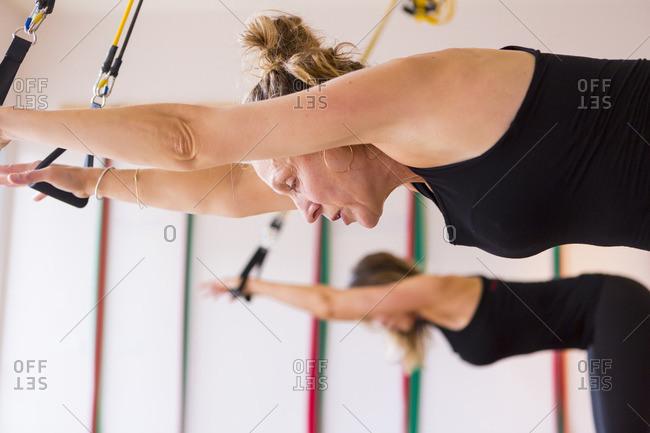 Caucasian women using resistance bands in gymnasium
