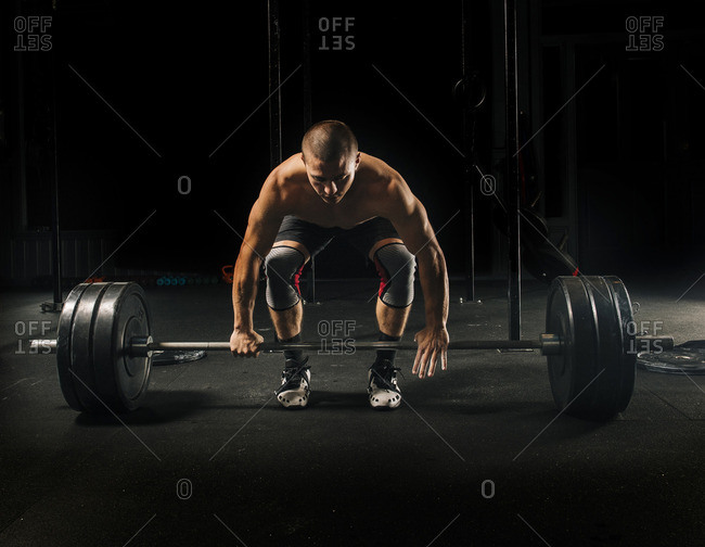Man lifting heavy barbell in gymnasium