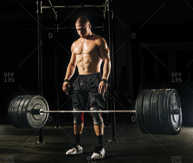 Man dropping heavy barbell in gymnasium