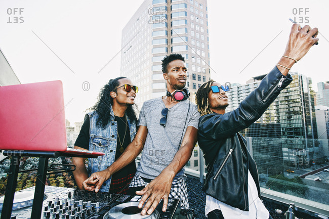 Men posing for cell phone selfie with DJ on urban rooftop