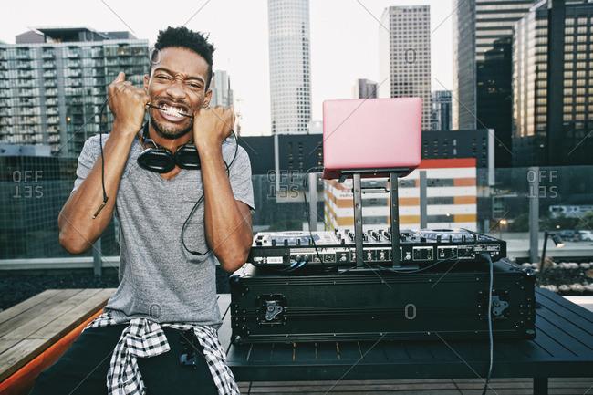 Black DJ biting headphones cord on urban rooftop