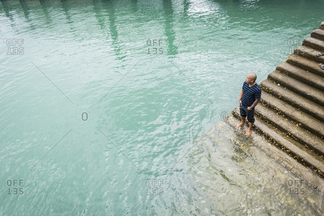 Chinese man standing on staircase in water