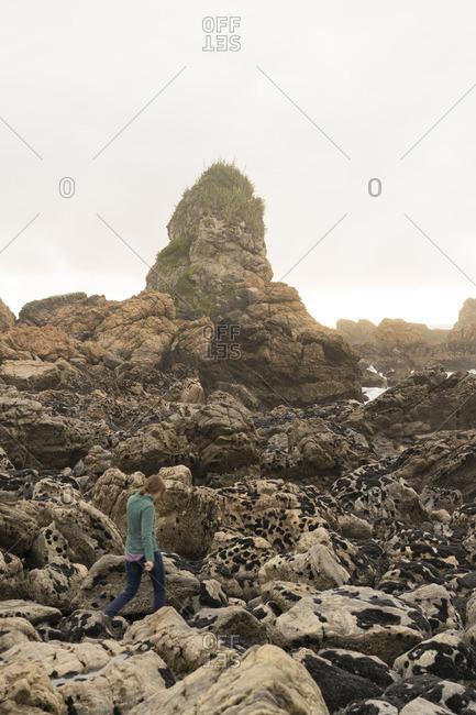 Caucasian woman walking on rocks