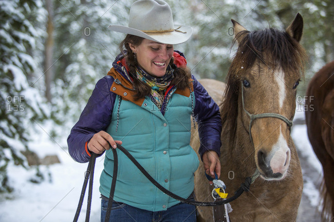 Smiling Caucasian woman holding rein of horse in winter