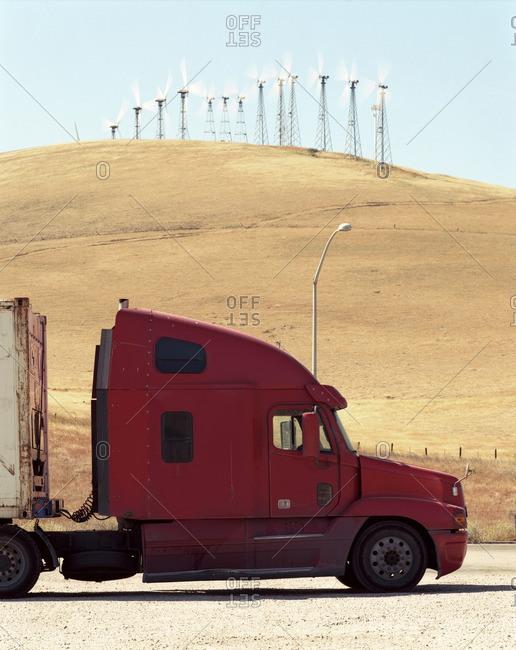 Red semi-truck parked near wind farm