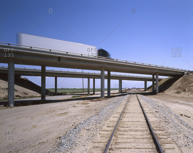 Trucks driving on freeway overpass over train track