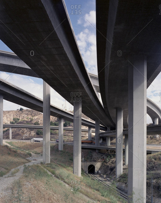 Trucks and cars driving under freeway overpass