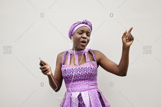 Black woman dancing to music on cell phone