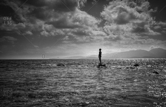 Silhouette of Caucasian boy standing on rock in ocean