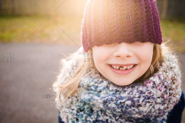 Little girl in a knit scarf with a toboggan over her eyes