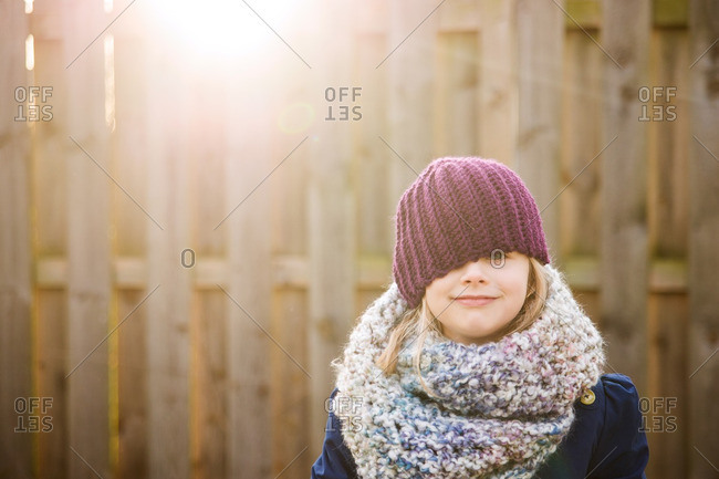 Little girl in a knit scarf and toboggan standing in front of a fence