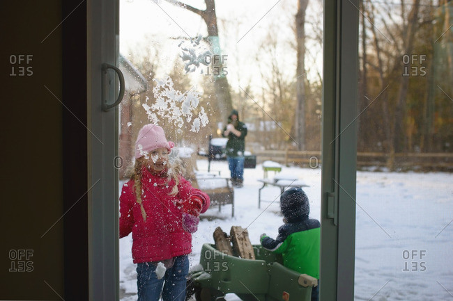 Father and two children playing with snowballs outdoors