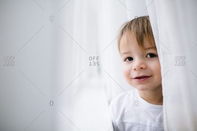 Portrait of a toddler standing in white curtains