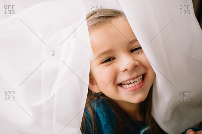 Portrait of a happy little girl standing in white curtains