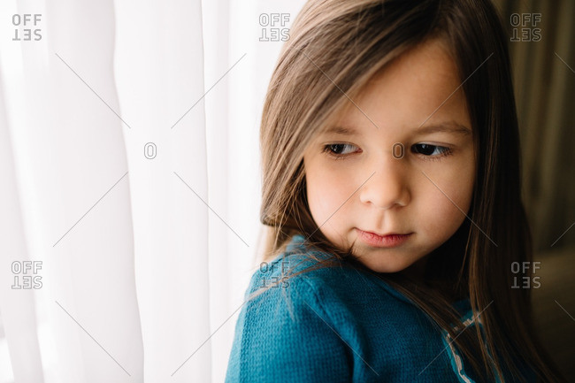 Little girl standing by white curtains